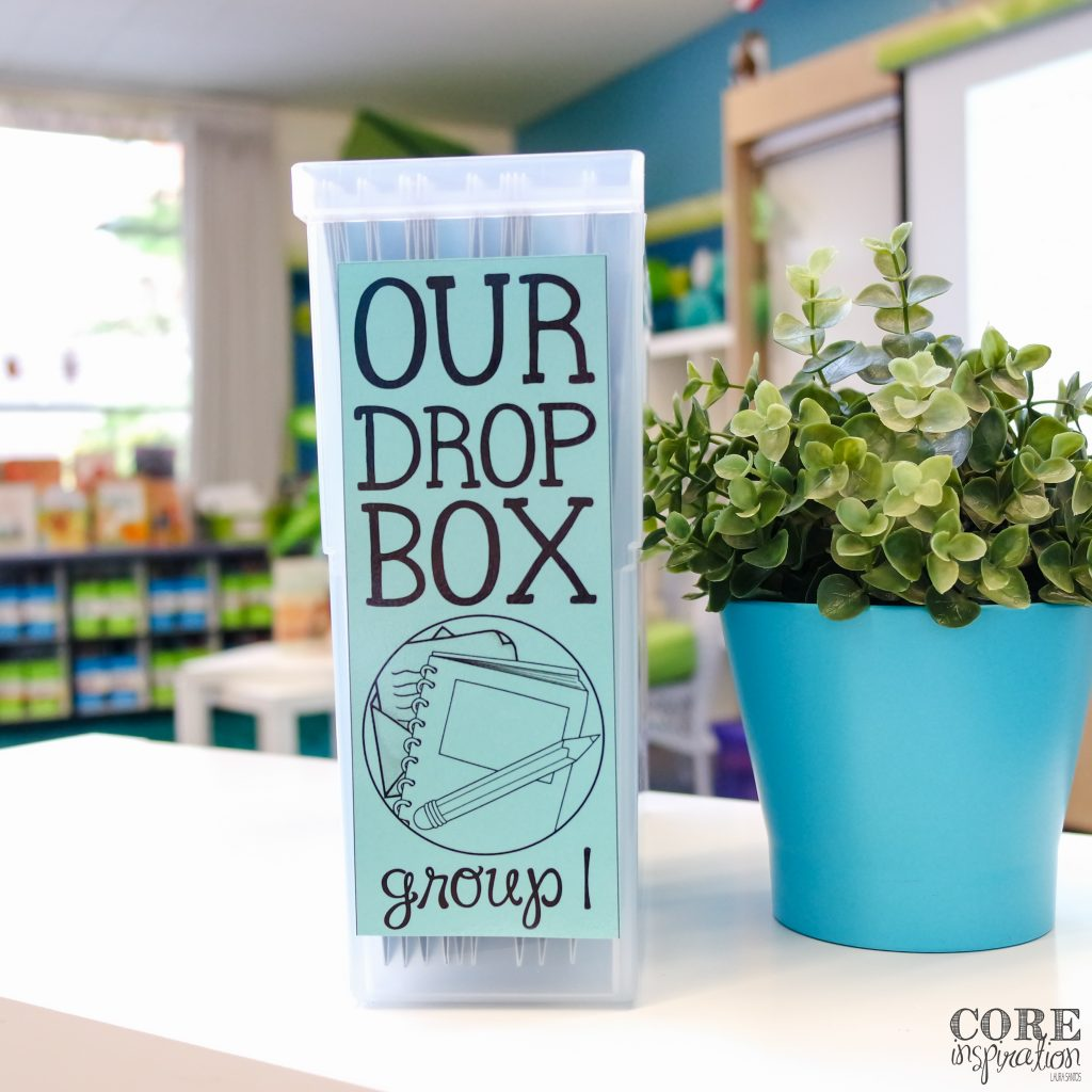 Core Inspiration Homework Drop Box sitting next to plant on top of white surface.