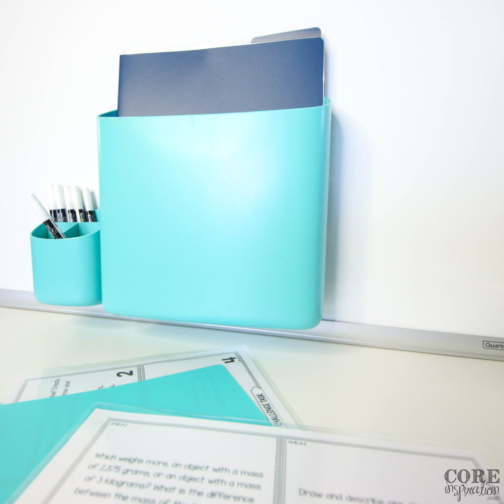 Plastic folder with word problem solving task cards placed inside a magnetic bin that is attached to a whiteboard is a sleek space-saving approach to storing task cards.
