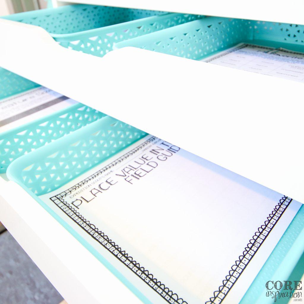 Core Inspiration's place value math project pages arrange in aqua paper bins inside a white drawer unit.