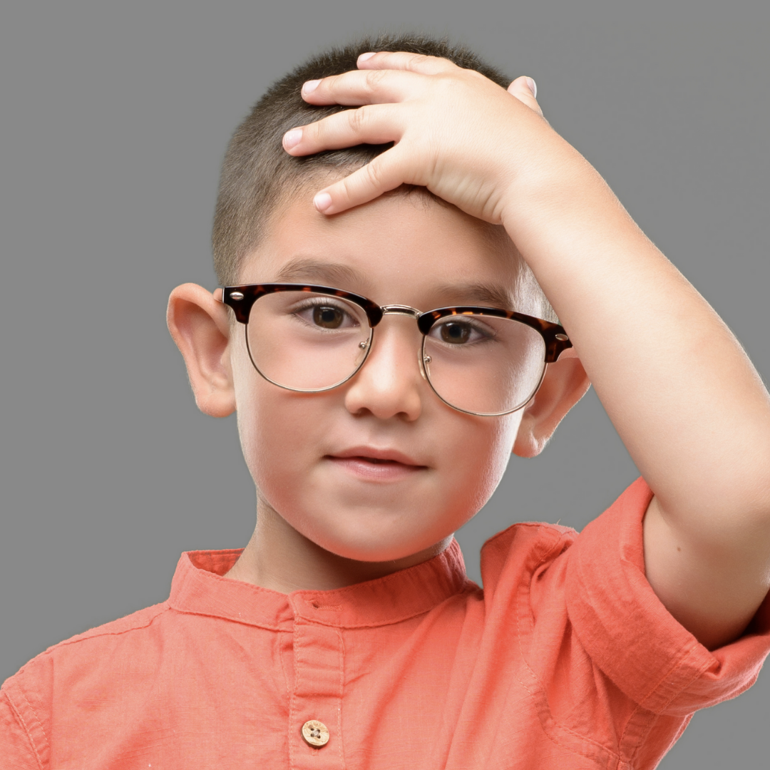 Little boy who wears glasses tapping his hand on his head to signal to the teacher that he's ready to have his work checked.